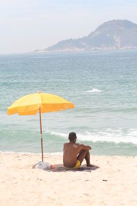 Man_sitting_under_beach_umbrella